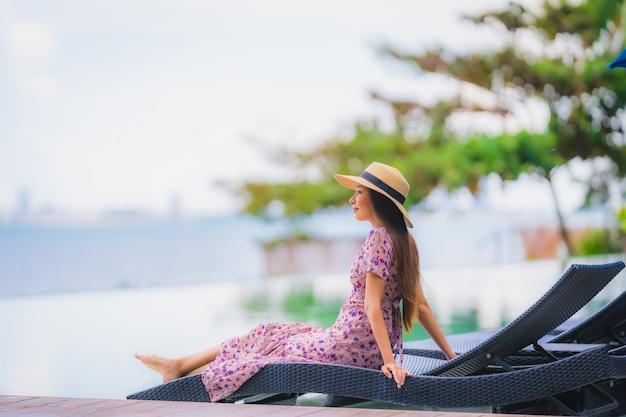 Retrato, bonito, jovem, mulher asian, feliz, sorrizo, relaxe, em, piscina, em, hotel, recurso, neary, mar, oceânicos, praia, ligado, céu azul