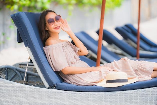 Retrato, bonito, jovem, mulher asian, ligado, a, convés, cadeira, com, guarda-chuva, ao redor, praia, oceano mar
