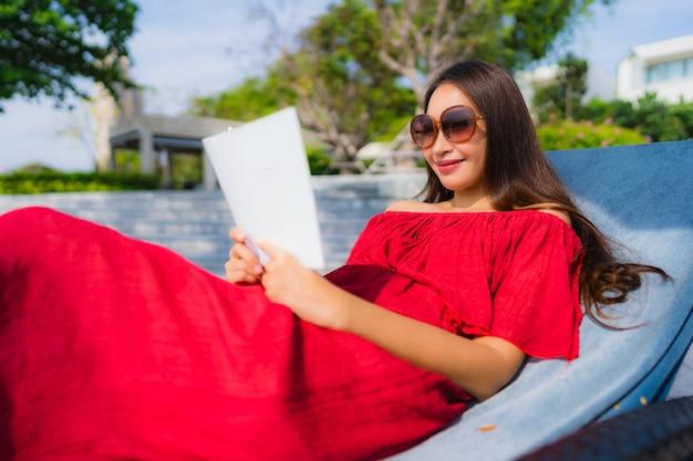 Retrato, bonito, jovem, mulher asian, livro leitura, em, piscina, em, hotel, e, recurso