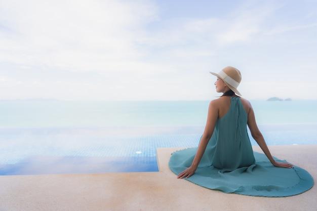 Retrato, bonito, jovem, mulher asian, relaxe, em, luxo, piscina ao ar livre, em, hotel, recurso, quase, praia, mar, oceânicos