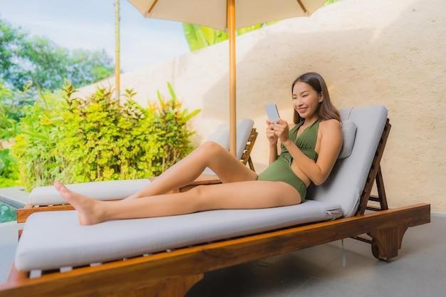 Retrato, bonito, jovem, mulher asian, sentando, ligado, a, plataforma cadeira, com, guarda-chuva, neary, piscina