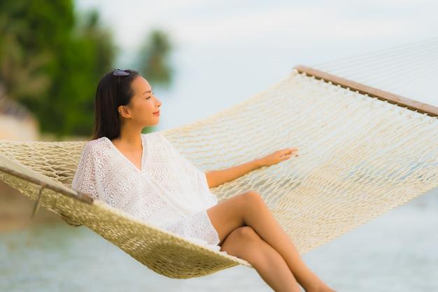 Retrato, bonito, jovem, mulher asian, sentando, ligado, rede, ao redor, mar, praia, oceânicos, para, relaxe