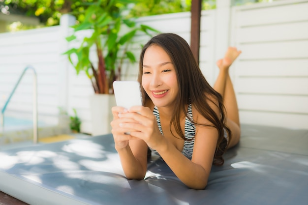 Retrato, bonito, jovem, mulher asian sorri, feliz, relaxe, com, telefone móvel, ao redor, piscina