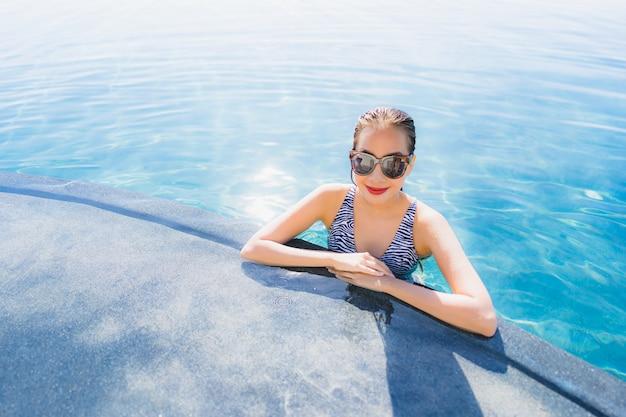 Retrato, bonito, jovem, mulher asian, sorrizo, feliz, relaxe, ao redor, piscina, em, hotel, recurso, para, lazer