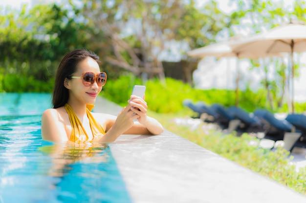 Retrato, bonito, jovem, mulher asian, usando, telefone móvel, ou, cellphone, em, a, piscina