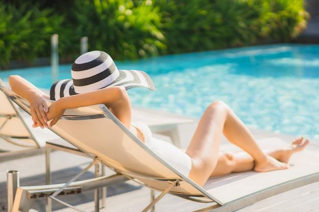 Retrato bonito jovem mulher asiática feliz sorrir e relaxar em torno da piscina no hotel resort