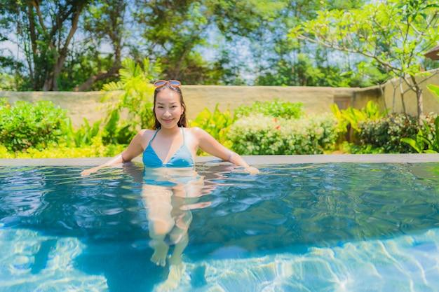 Retrato bonito jovem mulher asiática sorriso feliz relaxar e lazer na piscina
