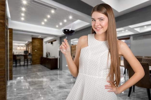 Retrato bonito modelo isolado sobre o estúdio, segurando o copo de vinho