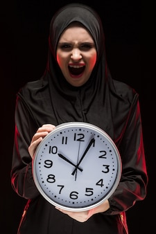 Retrato, bonito, sério, assustado, assustado, muçulmano, mulher jovem, desgastar, preto, hijab, segurando, relógio