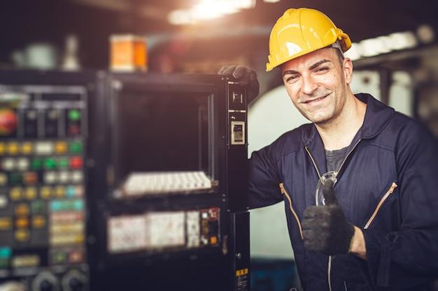 Retrato bonito sinal de mão de obra com traje de segurança no painel de controle da máquina na fábrica