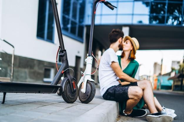 Retrato borrado de homem e mulher sentada e beijando perto de um edifício de vidro moderno. com suas scooters elétricas. em primeiro plano são os seus elétricos