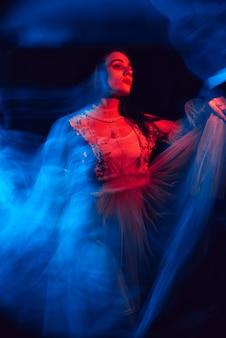 Retrato borrado e abstrato de uma jovem dançarina em um vestido com luz de néon vermelha e azul