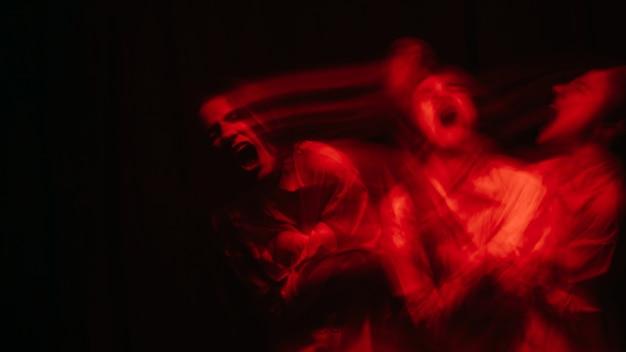 Retrato borrado e assustador de uma garota fantasma de bruxa em uma camisa branca em um fundo escuro