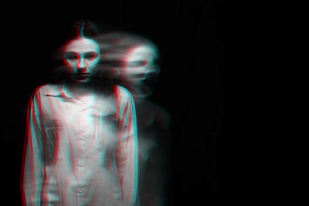 Retrato borrado e assustador de uma garota fantasma de bruxa em uma camisa branca sobre um fundo escuro. preto e branco com efeito de realidade virtual de falha 3d