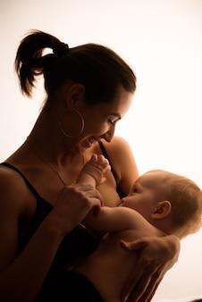 Retrato brilhante de uma mãe amamentando bebê.