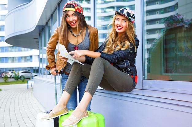 Retrato brilhante do estilo de vida ao ar livre das duas melhores amigas caminhando com suas malas perto do aeroporto