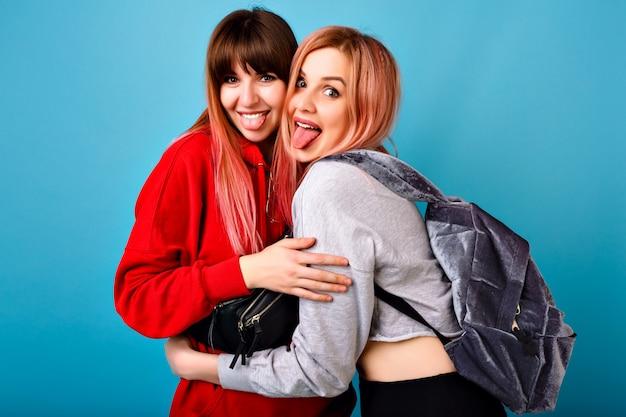 Retrato brilhante do estilo de vida do casal feliz de garotas hipster, mostrando as línguas e se abraçando, melhores amigos se divertindo, parede azul, vestindo moletons e mochila.
