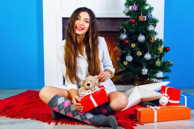 Retrato brilhante do estilo de vida interior de uma jovem bonita e feliz sentada em casa com a árvore de natal