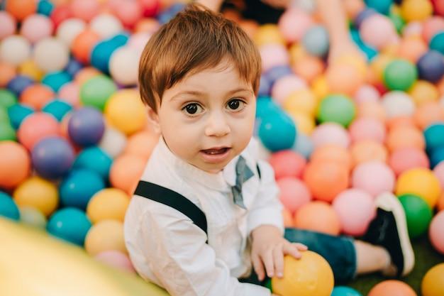 Retrato brilhante e colorido de um menino alegre sentado em um parquinho cheio de bolas coloridas