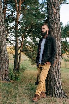 Retrato brutal, barbudo e bigode, lenhador hipster homem cigano na floresta com machado