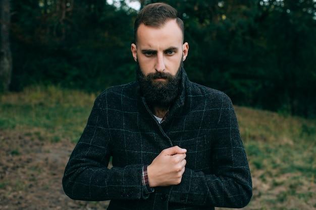 Retrato brutal, barbudo e bigode, lenhador hipster homem cigano na floresta