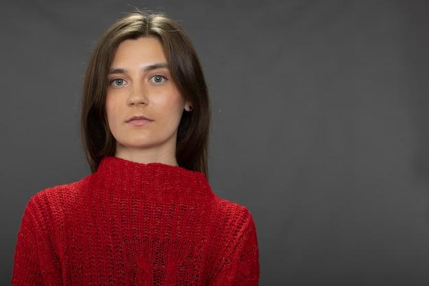 Retrato calmo de menina morena de cabelos compridos olhando para a frente com um suéter vermelho