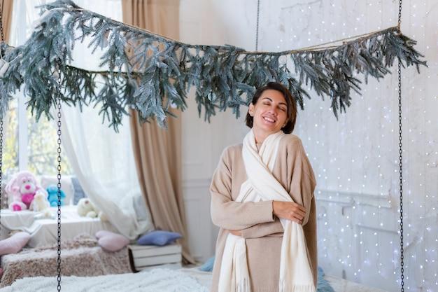 Retrato caloroso de mulher feliz em suéter, jeans e lenço branco em casa no quarto