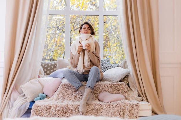 Retrato caloroso de mulher sentada no parapeito da janela com uma xícara de chá quente, café, suéter e lenço branco