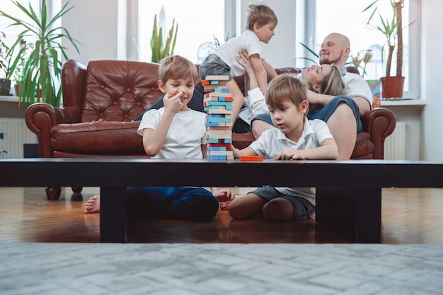 Retrato caloroso de uma família amorosa e feliz em casa. os meninos jogam jogo de tabuleiro e aproveitam as férias juntos na sala de estar.