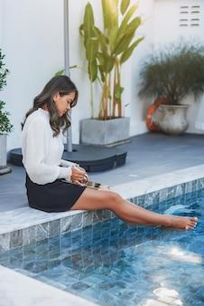 Retrato caloroso de uma menina asiática focada, ela usa seu tablet moderno e gosta de piscina durante o dia.