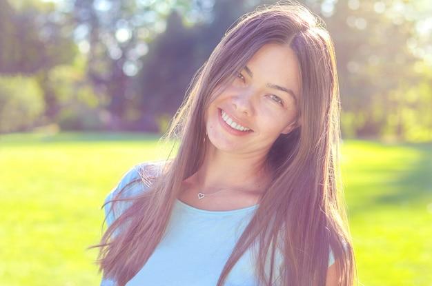 Retrato cândido da mulher bonita de sorriso feliz ao ar livre, beleza natural da menina sem composição.