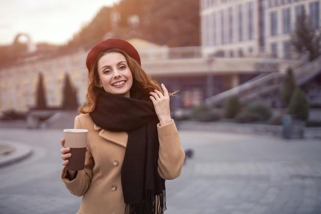 Retrato casual de uma mulher francesa segurando uma caneca de café do lado de fora em um casaco bege de outono e boina vermelha com