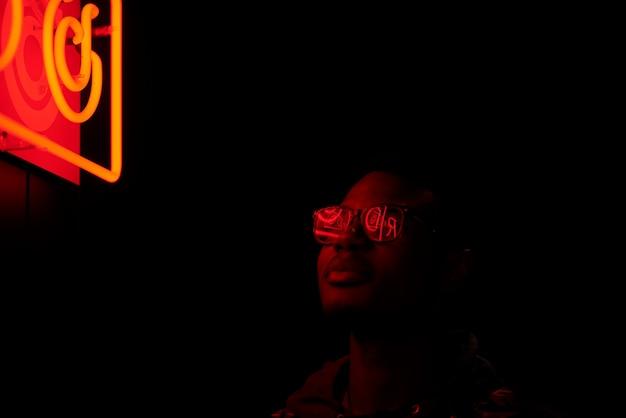 Retrato cinematográfico de homem bonito com óculos de sol com luzes de neon legais