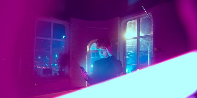 Retrato cinematográfico de um jovem bonito em um interior iluminado por neon