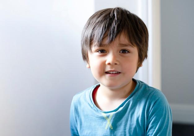 Retrato claro chave da altura do menino bonito que olha a câmera com cara de sorriso.
