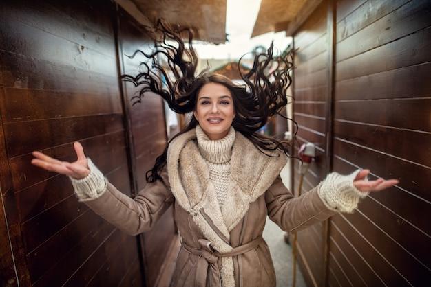 Retrato close-up vista de satisfeito alegre elegante atraente linda jovem feliz no suéter e jaqueta, olhando para a câmera, mantendo os braços abertos no meio de duas paredes de madeira.