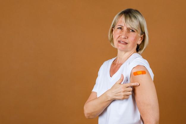 Retrato closeup estúdio tiro de paciente caucasiano sênior loira ficar estressando tem dor com ferida de injeção em bandagem de gesso laranja em seu ombro após receber a vacinação covid-19.