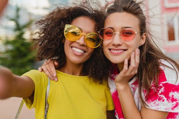 Retrato colorido de felizes amigas jovens sorrindo sentadas na rua tirando uma foto de selfie no celular, mulheres se divertindo juntas
