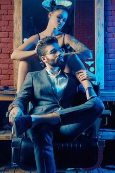 Retrato colorido de lindo casal: homem brutal em um terno elegante e uma garota sexy com uma tatuagem de lingerie na barbearia