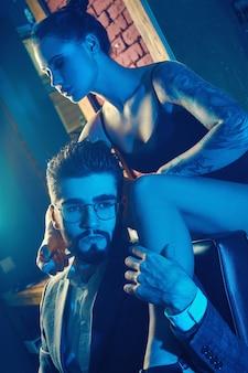 Retrato colorido de lindo casal. homem de terno elegante e garota com uma tatuagem de lingerie na barbearia