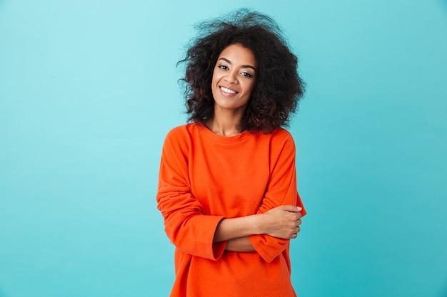 Retrato colorido de mulher incrível na camisa vermelha com penteado afro, olhando com sorriso, isolado sobre a parede azul