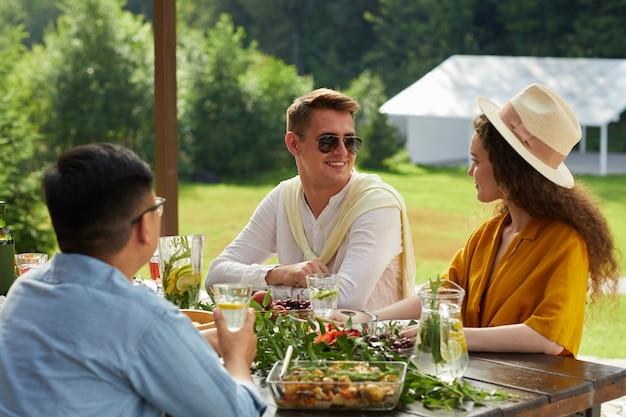 Retrato colorido de um jovem casal sorridente conversando enquanto jantava com amigos ao ar livre durante a festa de verão