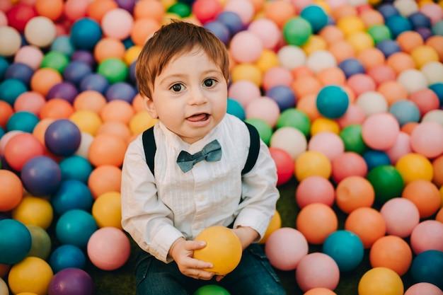 Retrato colorido de um menino engraçado em um parquinho cheio de bolas coloridas segurando uma bola laranja