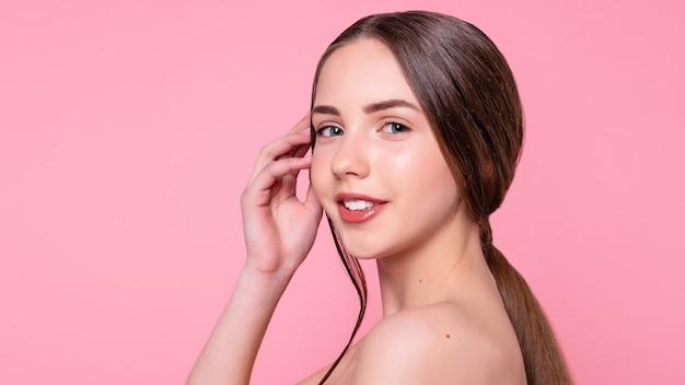 Retrato com espaço de cópia de menina charmosa, alegre, trendy, atraente, adorável, nua, sem camisa com maquiagem moderna, pele perfeita, ideal, isolada no fundo rosa. formato panorâmico 16: 9.