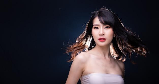 Retrato com metade do corpo de 20 mulheres asiáticas em estilo de alta moda e cabelo jogado no ar sobre um fundo preto com luz de fundo iluminada por trás, copie o espaço