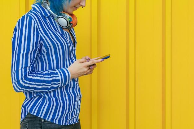 Retrato com telefone inteligente nas mãos usando wi-fi 4g isolado em amarelo