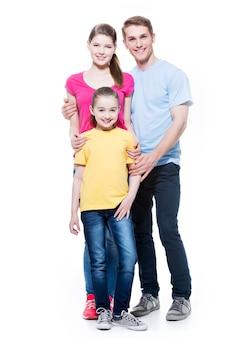 Retrato completo da jovem família feliz com a filha em camisas multicoloridas - isoladas na parede branca.