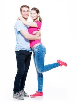 Retrato completo de casal atraente feliz isolado na parede branca.