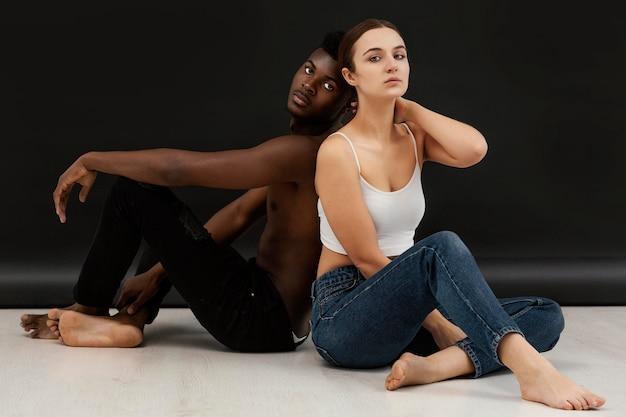 Retrato completo de homem negro e mulher branca posando