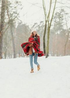 Retrato completo de mulher caminhando na neve